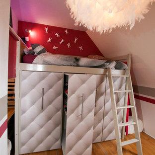 Modelo de dormitorio infantil moderno, de tamaño medio, con paredes rosas y suelo de madera clara