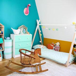 Aménagement d'une chambre d'enfant de 1 à 3 ans scandinave avec un mur multicolore et un sol en bois brun.