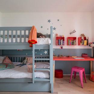 Cette image montre une chambre de fille de 4 à 10 ans design de taille moyenne avec un bureau, un sol en bois clair et un mur multicolore.