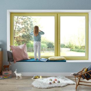 Inspiration pour une grand chambre d'enfant de 4 à 10 ans design avec un mur bleu, un sol en bois clair et un sol beige.