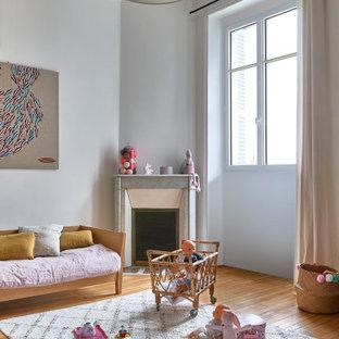 Aménagement d'une chambre d'enfant de 1 à 3 ans contemporaine de taille moyenne avec un mur gris, un sol en bois brun et un sol marron.