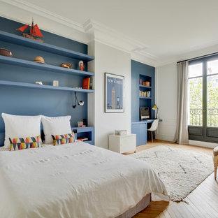 Exemple d'une grande chambre d'enfant chic avec un mur bleu et un sol en bois brun.