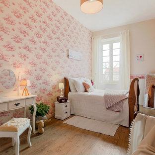 Réalisation d'une chambre d'enfant tradition avec un mur rose, un sol en bois clair et un sol marron.