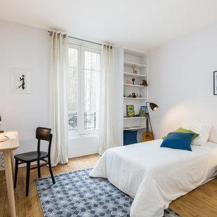 Cette photo montre une chambre d'enfant de 4 à 10 ans tendance avec un mur blanc et un sol en bois brun.