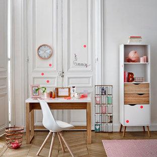 Idée de décoration pour une chambre d'enfant nordique de taille moyenne avec un bureau, un mur blanc et un sol en bois brun.