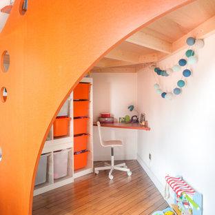 Aménagement d'une chambre neutre de 4 à 10 ans contemporaine de taille moyenne avec un bureau, un mur blanc et un sol marron.