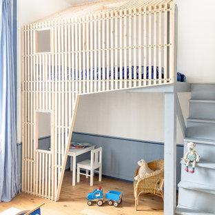Modelo de dormitorio infantil de 4 a 10 años, contemporáneo, de tamaño medio, con paredes blancas, suelo de madera clara y suelo beige
