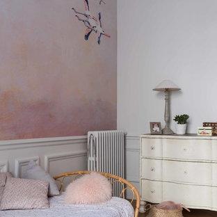 Réalisation d'une chambre d'enfant tradition avec un mur rose, un sol en bois clair et un sol beige.