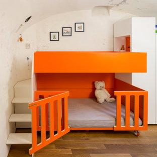 Idées déco pour une chambre d'enfant de 1 à 3 ans contemporaine avec un mur beige et un sol en bois brun.