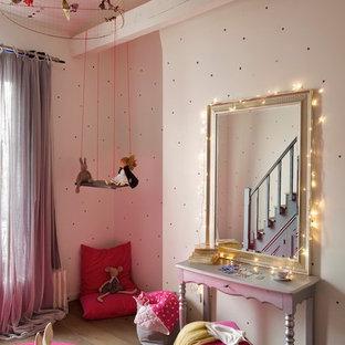 Aménagement d'une grande chambre d'enfant de 4 à 10 ans contemporaine avec un sol en bois brun et un mur beige.