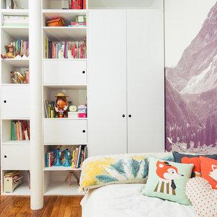 Inspiration pour une chambre d'enfant de 4 à 10 ans design avec un sol en bois brun et un mur blanc.