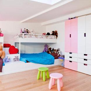 Aménagement d'une grand chambre d'enfant de 4 à 10 ans contemporaine avec un mur blanc et un sol en bois clair.