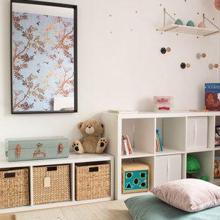 Exemple d'une chambre d'enfant chic avec un mur blanc et un sol en bois clair.
