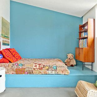Exempel på ett mellanstort modernt pojkrum kombinerat med sovrum och för 4-10-åringar, med blå väggar och betonggolv
