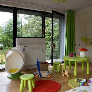 Aménagement d'une chambre d'enfant de 1 à 3 ans contemporaine de taille moyenne avec un sol en bois brun.