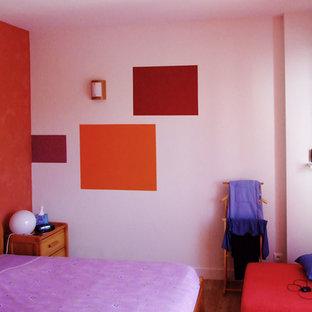Idées déco pour une petite chambre d'enfant contemporaine avec un mur orange, sol en stratifié et un sol marron.