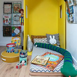 Réalisation d'une chambre d'enfant de 4 à 10 ans design de taille moyenne avec un mur blanc, un sol en bois brun et un sol beige.