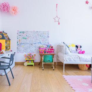 Modern inredning av ett stort flickrum kombinerat med sovrum och för 4-10-åringar, med vita väggar och ljust trägolv