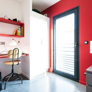 Modern inredning av ett mellanstort barnrum kombinerat med sovrum, med röda väggar, betonggolv och grått golv