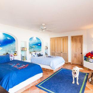 На фото: детская в средиземноморском стиле с спальным местом, белыми стенами и полом из терракотовой плитки для ребенка от 4 до 10 лет, мальчика с