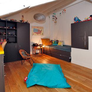 Aménagement d'une chambre d'enfant contemporaine avec un mur blanc, un sol en bois brun et un sol marron.
