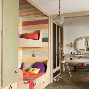 Idée de décoration pour une chambre d'enfant de 4 à 10 ans bohème avec un mur multicolore et un sol en bois brun.