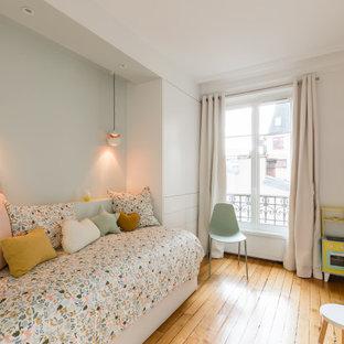 Idée de décoration pour une chambre d'enfant design avec un mur blanc, un sol en bois brun et un sol marron.