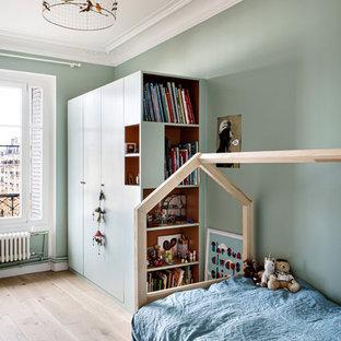 Réalisation d'une chambre d'enfant de 4 à 10 ans design de taille moyenne avec un mur bleu et un sol en bois clair.
