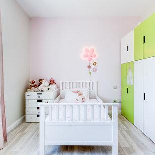 Cette photo montre une chambre d'enfant de 1 à 3 ans tendance de taille moyenne avec un sol en bois clair et un mur multicolore.