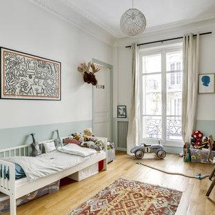 Cette photo montre une chambre d'enfant de 1 à 3 ans scandinave avec un mur multicolore, un sol en bois clair et un sol beige.