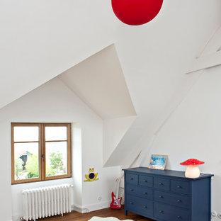 Aménagement d'une chambre d'enfant de 4 à 10 ans contemporaine de taille moyenne avec un mur blanc et un sol en bois brun.