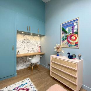 Inspiration pour une chambre d'enfant design de taille moyenne avec un bureau, un mur bleu, un sol en bois brun et un sol beige.