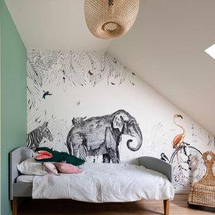 Réalisation d'une chambre d'enfant de 4 à 10 ans nordique avec un mur multicolore, un sol en bois clair et un sol beige.