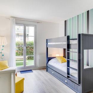 Esempio di una cameretta per bambini da 4 a 10 anni scandinava di medie dimensioni con pareti verdi, pavimento in laminato e pavimento marrone