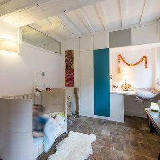 Inspiration pour une chambre d'enfant de 1 à 3 ans design avec un mur blanc et un sol en carreau de terre cuite.