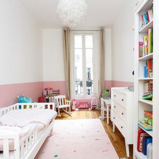 Réalisation d'une chambre d'enfant de 1 à 3 ans nordique de taille moyenne avec un sol en bois brun, un mur rose et un sol marron.