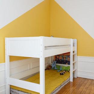 Ispirazione per una cameretta per bambini da 4 a 10 anni scandinava di medie dimensioni con pareti gialle, pavimento in legno massello medio e pavimento marrone