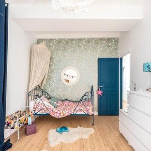 Exemple d'une chambre d'enfant tendance avec un mur bleu, un sol en bois clair et un sol beige.