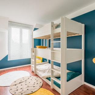 Cette photo montre une chambre d'enfant tendance de taille moyenne avec un mur bleu, un sol en bois brun et un sol marron.