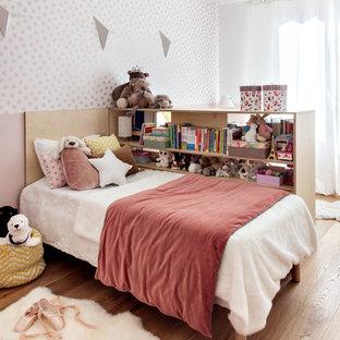 Idées déco pour une chambre d'enfant contemporaine avec un mur rose, un sol en bois brun et un sol marron.