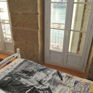 Cette photo montre une grande chambre d'enfant moderne avec un mur blanc, un sol en carreau de terre cuite et un sol marron.