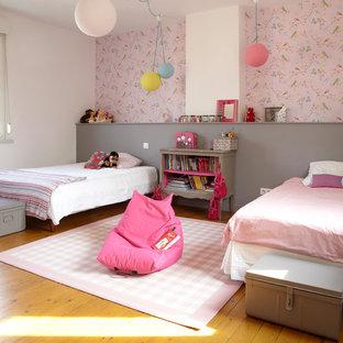 Aménagement d'une grande chambre d'enfant de 4 à 10 ans contemporaine avec un sol en bois clair et un mur multicolore.