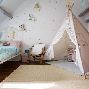 Example of a mid-sized cottage chic girl brown floor and medium tone wood floor kids' room design in Paris with white walls