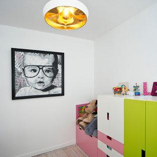 Aménagement d'une chambre d'enfant de 1 à 3 ans contemporaine de taille moyenne avec un mur blanc et un sol en bois clair.