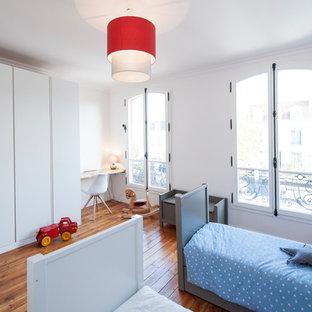 Cette image montre une chambre d'enfant de 4 à 10 ans nordique avec un mur blanc, un sol en bois brun et un sol marron.
