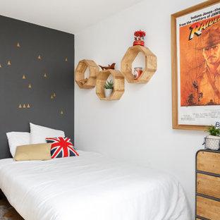 Idées déco pour une chambre de garçon contemporaine avec un mur gris, un sol en bois brun et un sol marron.