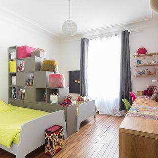 Idées déco pour une chambre d'enfant contemporaine avec un mur blanc, un sol en bois brun et un sol marron.