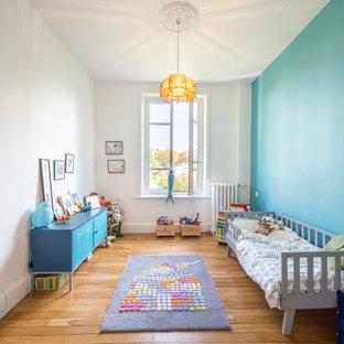 Aménagement d'une chambre d'enfant de 4 à 10 ans classique de taille moyenne avec un mur bleu, un sol marron et un sol en bois brun.