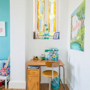 Cette photo montre une chambre de garçon de 4 à 10 ans chic de taille moyenne avec un bureau, un mur bleu, un sol marron et un sol en bois brun.