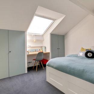Modelo de dormitorio infantil actual, grande, con paredes blancas, moqueta y suelo azul